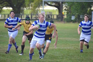 Jesuit High School student Chuck Lobrano (center) battles against Brother Martin High School during a club rugby game.