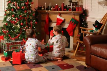 children looking at gifts under christmas tree